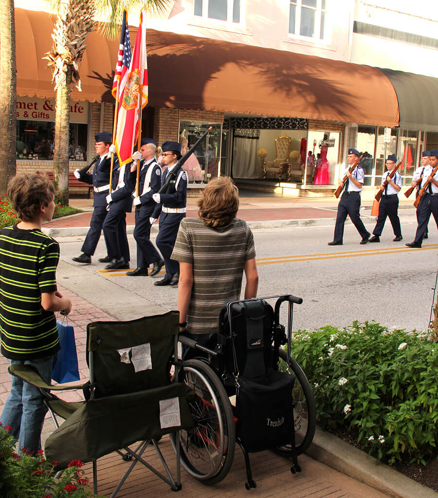 photo of high school teen trying to stand for the flag from a conventional wheelchair
