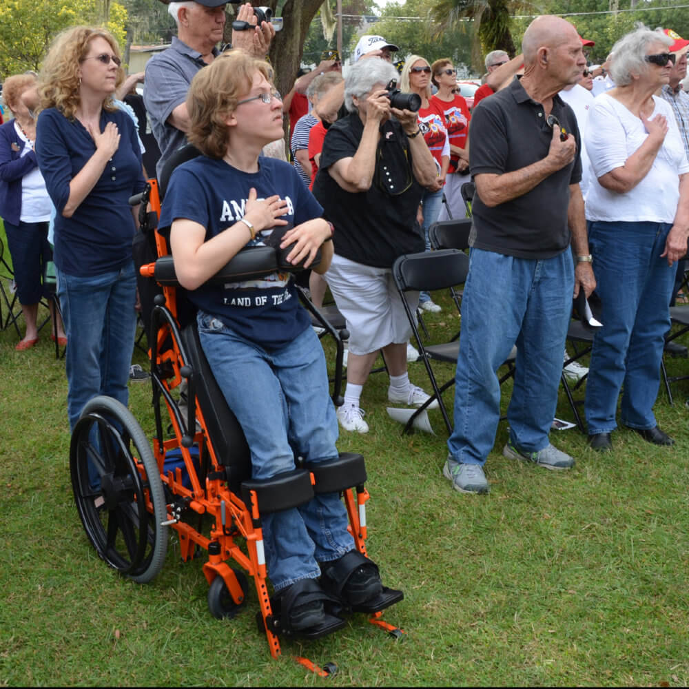 Arek Trenholm stands for the pledge of allegiance in his manual power standing wheelchair