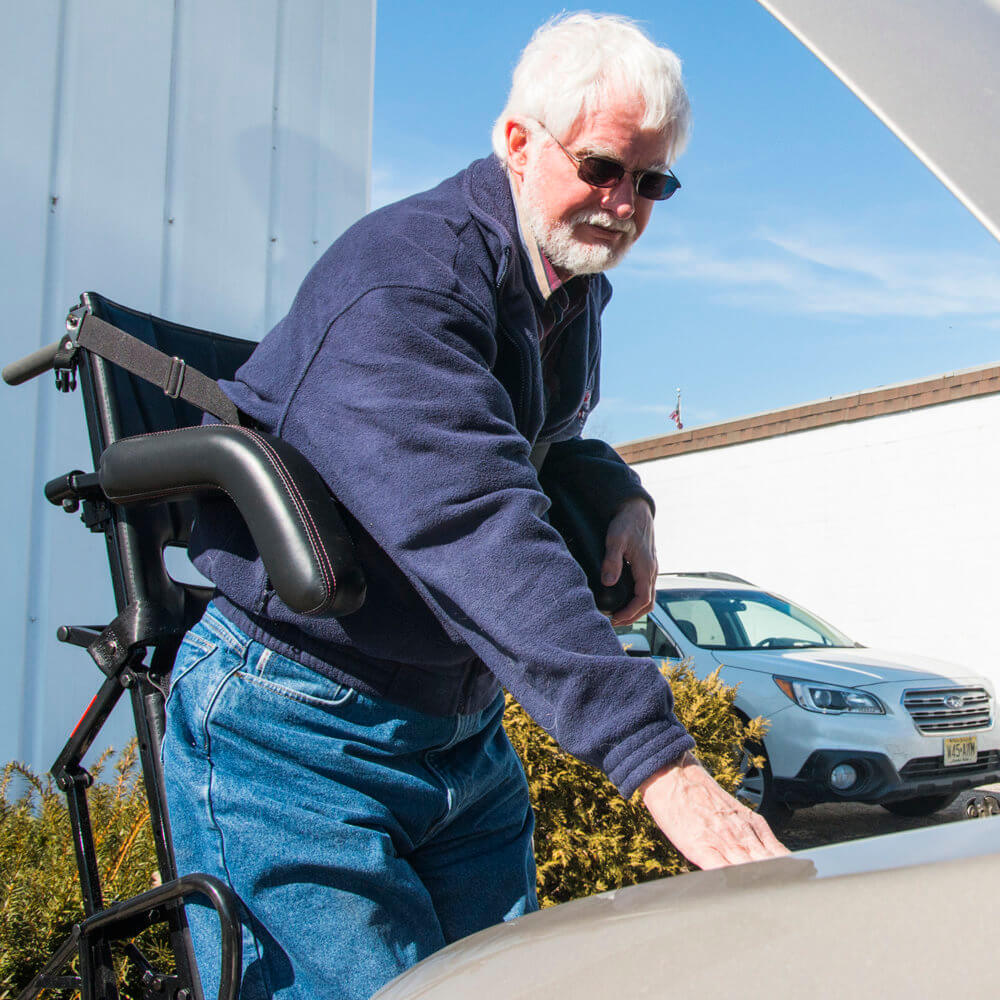 man working on car from standing wheelchair